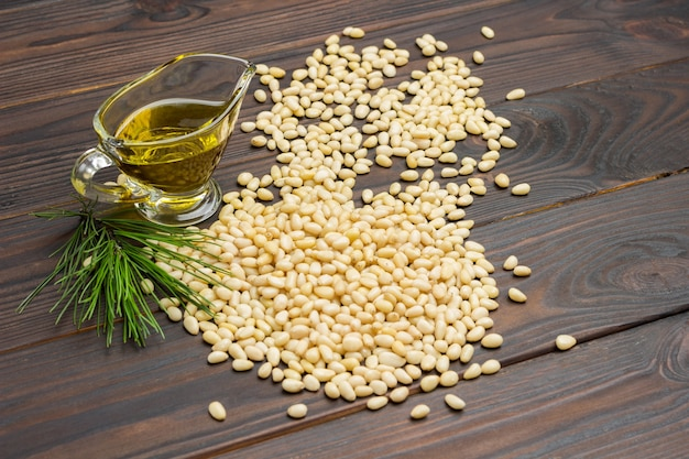 Pine nuts and cedar oil on wooden board