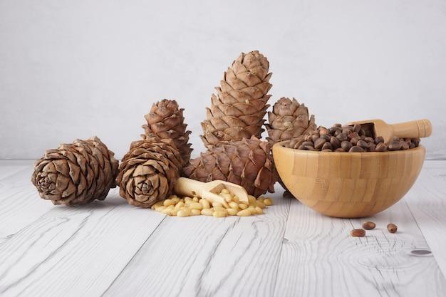 Кедровые орехи в бамбуковой миске рядом с кедровыми шишками на свету.