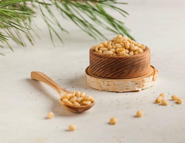 Кедровые орехи в деревянной миске и деревянной ложкой на фоне хвойной ветки.