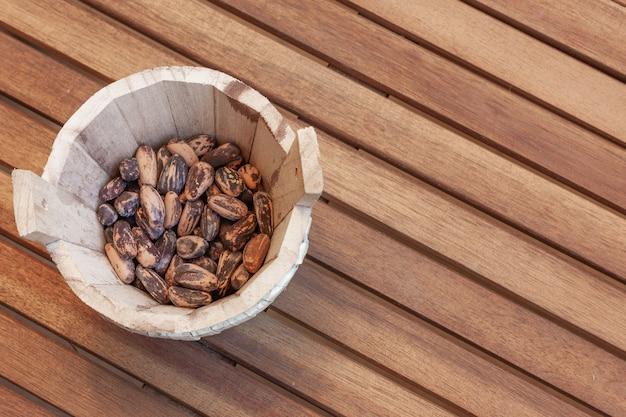 木製のテーブルの上の木製のボウルに松の実