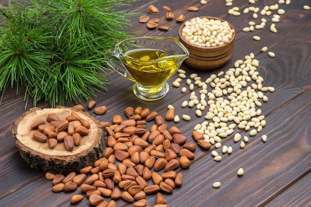 Кедровые орехи, масло кедрового ореха и кедровая ветка. темный деревянный фон. вид сверху.