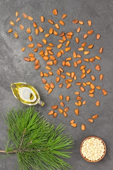 Pine nuts, pine nut oil and cedar branch on grey concrete. flat lay.