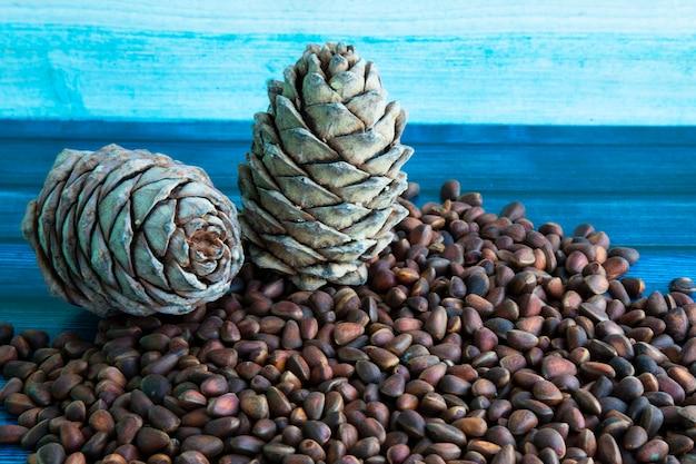 소나무 견과류. 나무 테이블에 소나무 견과류와 콘입니다. 껍질에 시베리아 소나무의 씨앗입니다. 적절한 영양