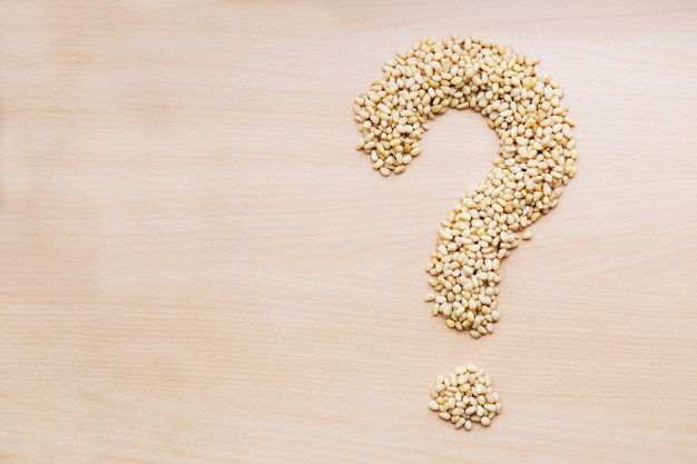 Pine nuts in the shape of question mark on light wooden background. template of nuts on the table