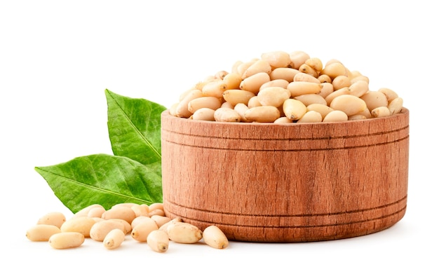 Pine nuts in a wooden plate with green leaves close-up on a white background. isolated