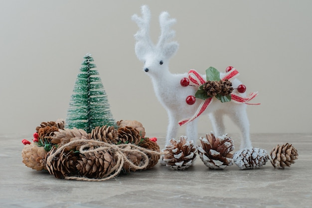 Pine tree, cones and toy deer on marble table.