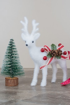 Pine tree and toy deer on marble table.