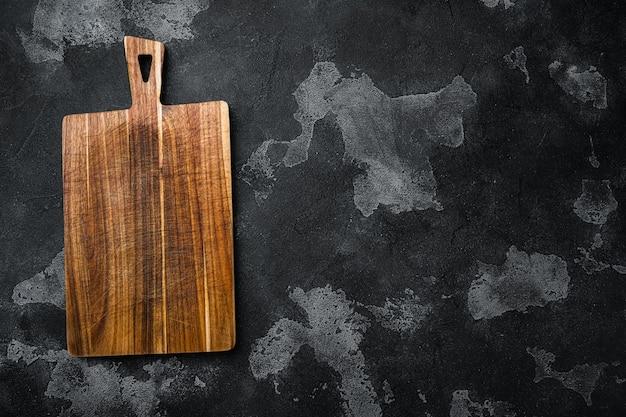 검은색 짙은 석재 테이블 배경에 있는 소나무 절단 보드 세트, 텍스트 또는 제품을 위한 복사 공간이 있는 평면도