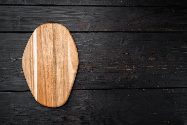 Набор деревянных разделочных досок из сосны, на фоне черного деревянного стола, плоская планировка, вид сверху, с копией пространства для текста или вашего продукта