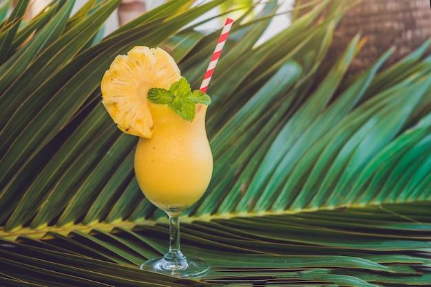 Ананасовые и ананасовые смузи на поверхности ветки пальмы
