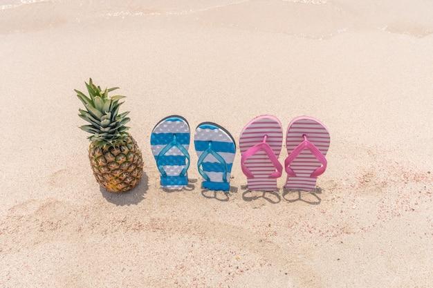 熱帯のビーチでのパイナップルとスリッパ