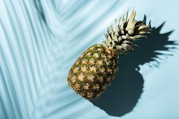 青い背景にパイナップルと熱帯のヤシの葉