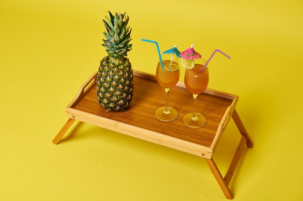 Украшенный ананас и два бокала с экзотическими летними коктейлями