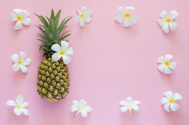ピンクの背景にパイナップルと白いフランジパニの花