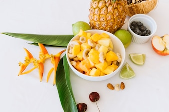 Pineapple; banana and apple salad in white bowl with lemons