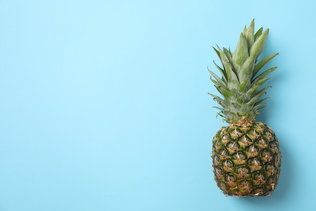 Pineapple on blue background, space for text. juicy fruit