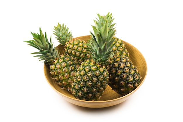 Pineapple in a bowl isolated om white.