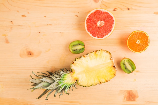 Pineapple and citrus fruits on wooden table