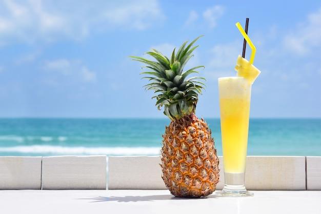 Ананасовый коктейль и спелый ананас на белой деревянной стойке пляжного бара с видом на море