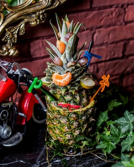 Pineapple cocktail served in pineapple with tangerine and pear slices