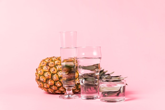 Pineapple behind containers of water