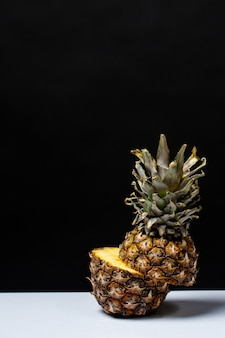 Pineapple cut in half on a table on a black