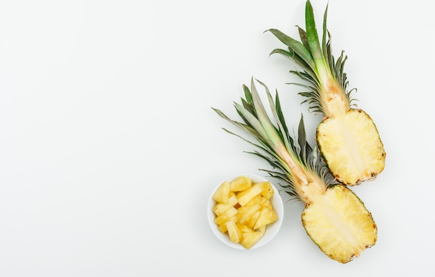 Pineapple cut in halves and slices in a white bowl on a white. flat lay.