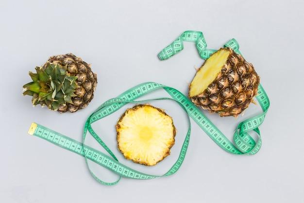 パイナップルを細かく切り、巻尺。灰色の背景。フラットレイ