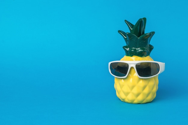Pineapple figurine in sunglasses on a blue background. summer concept.