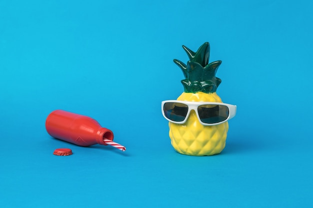 A pineapple figurine with sunglasses and a fallen red bottle on a blue background. summer concept.