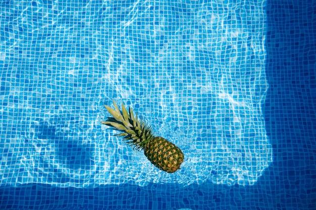 スイミングプールの背景の波状の水面に浮かぶパイナップル。夏のコンセプト。