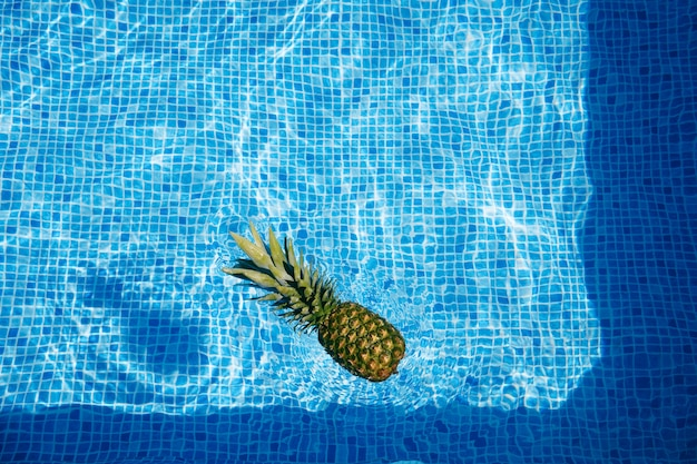 Pineapple floating on wavy water surface of swimming pool background. summer concept.