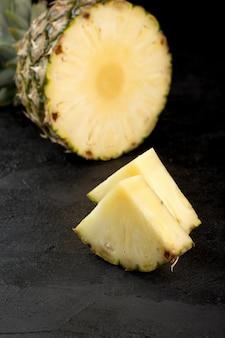 灰色の床に分離されたパイナップルの新鮮な熟したジューシーなまろやかなスライス
