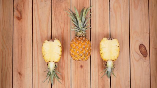 木製の背景にパイナップルの果実とその断片