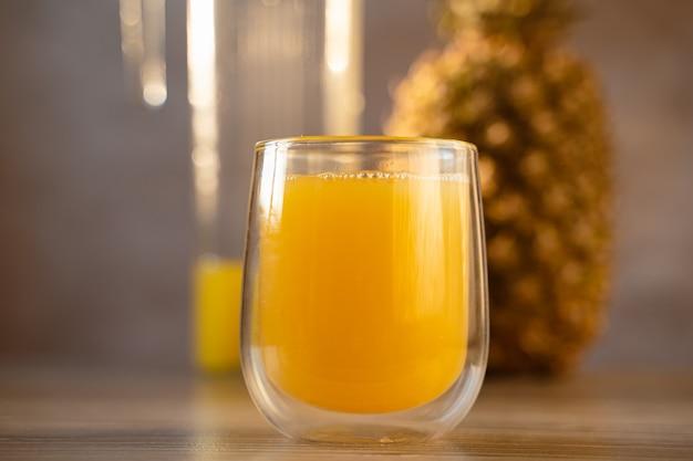 パイナップルフルーツとジュースをダブルグラスカップに入れます。トロピカルフルーツ 。黄色いトロピカルジュースをグラスに注ぐ。