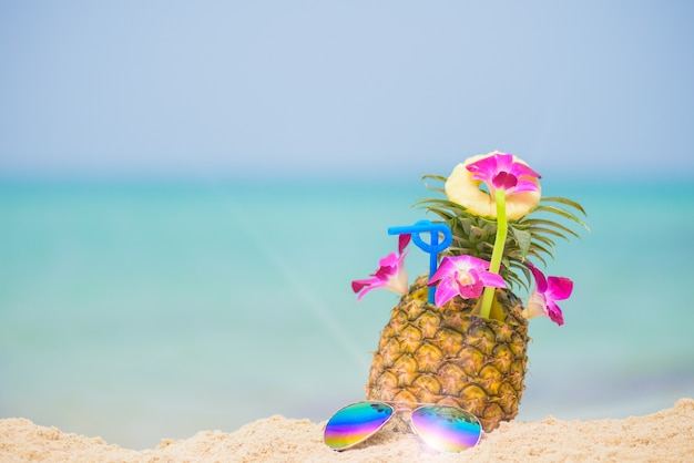 Pineapple fruit on beach with blue sea background, summer fruit drink concept.