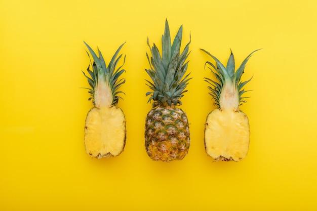 黄色の夏の背景にパイナップルフルーツ。夏の明るい黄色の背景にミニマリストスタイルの全体の熱帯パイナップルと半分の果物。フラットレイ。