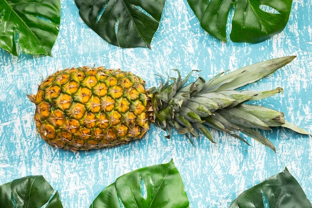 Pineapple fruit with monstera leaves