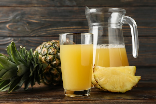 Pineapple, glass jug and glass with juice on wood, space for text