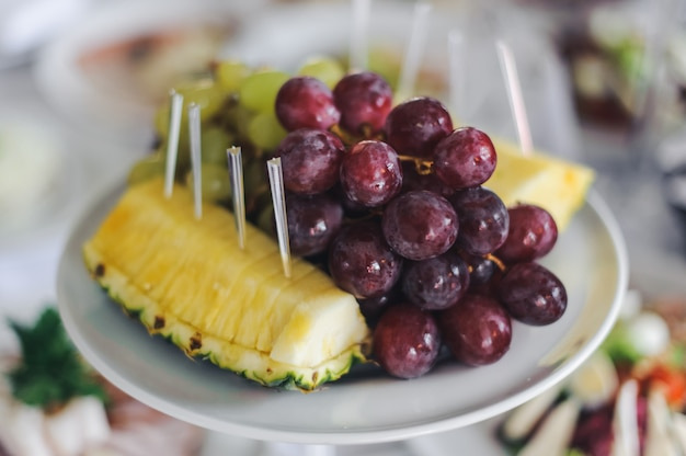 Pineapple and grape served on white plate