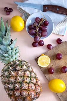 Pineapple, grapes and lemons on cutting board on table. healthy fresh juicy fruits background, vegan vegetarian food