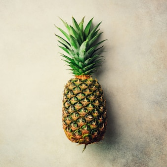 Pineapple on gray background, top view, copy space. minimal design. vegan and vegetarian concept.