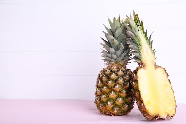 Pineapple and half of pineapple on a white wooden table