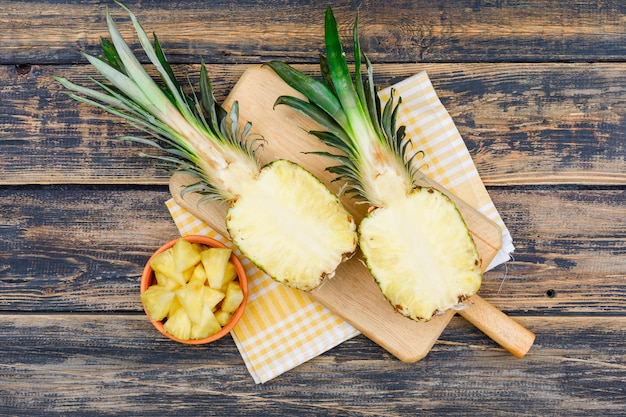 Pineapple halves and slices in a clay bowl and cutting board on old wood grunge surface and picnic cloth, flat lay.