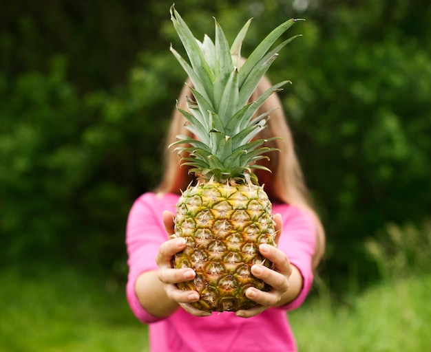 Pineapple in hands of a beautiful woman