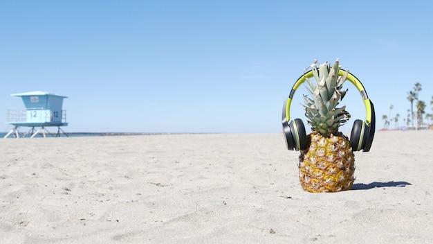 Pineapple in headphones, sandy ocean beach coast. tropical summer exotic fruit. ananas on shore.