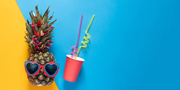 Pineapple in heart shapped sunglasses and plastic cup with straws on half blue and yellow background