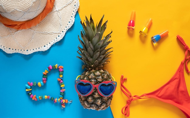 Pineapple in heart shapped sunglasses, straw hat and more summer accesories on yellow background