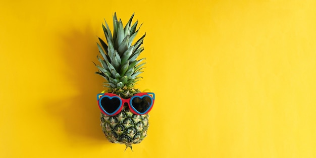 Pineapple in heart shapped sunglasses on yellow background with copy space