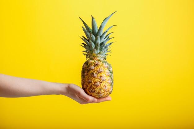 女性の手にパイナップル。黄色の背景に分離された熟したジューシーなパイナップルトロピックフルーツ。コピースペースを備えたミニマルな夏のコンセプト。高品質のストックフォト。